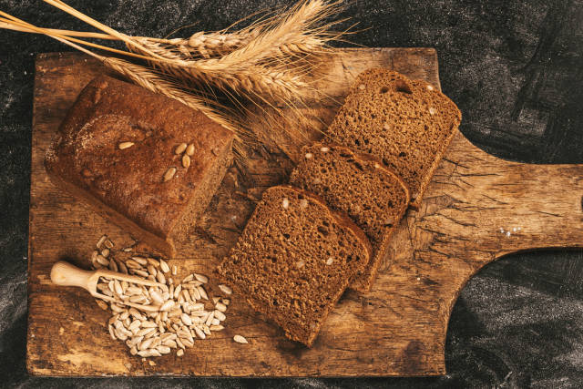 Top view, black bread with sunflower seeds in a wooden scoop and ears of wheat on an old cutting board