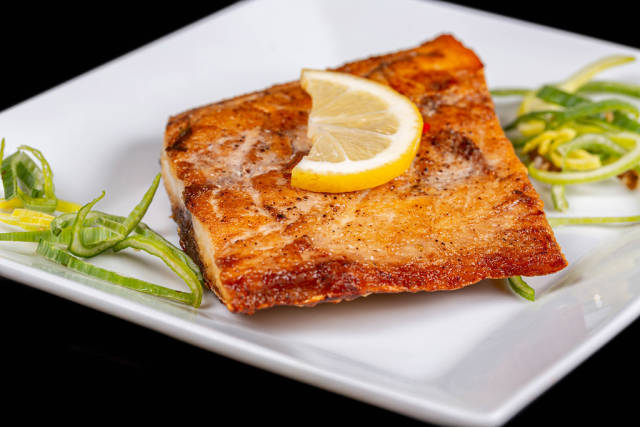 Grilled tuna steak with a slice of lemon on a white plate