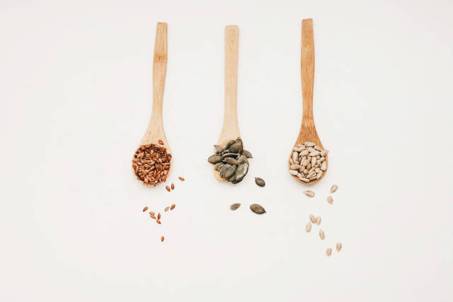 Top view of three wooden spoons with flaxseed, pumpkin seed and sunflower seed on white background