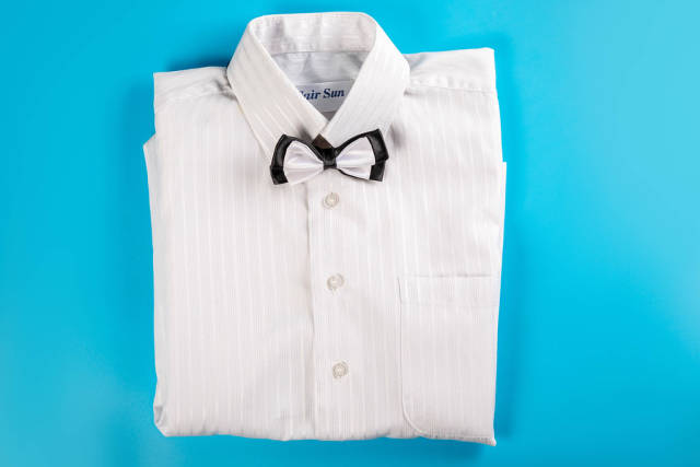 Childrens white shirt with bow tie on blue, top view