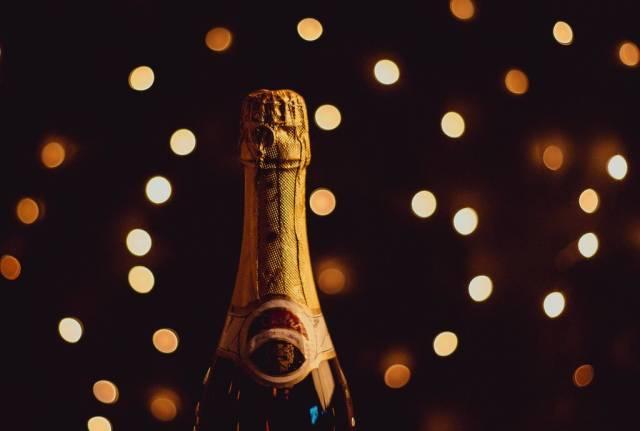 Champagnerflasche in festlicher Atmosphäre vor Lichtermeer im Hintergrund
