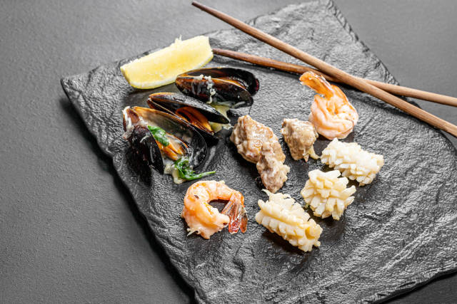 Mussels, shrimp, squid and fish on a black stone background