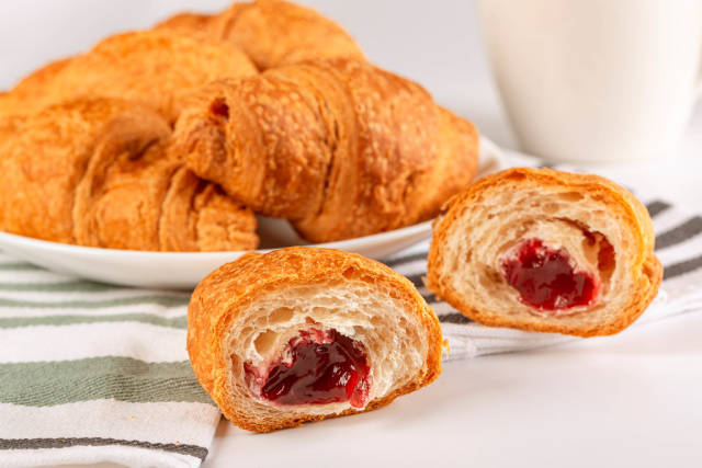 Croissants with fruit jam on the kitchen table