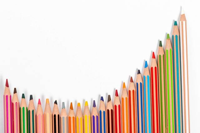 School background with many colorful pencils on white background