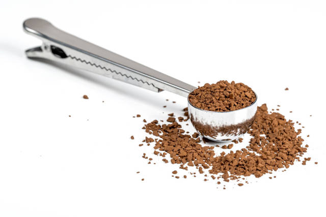 Measuring spoon with instant coffee on a white background