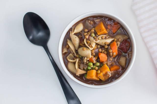 Braune Suppe mit Pasta, Karotten, Kürbis, Erbsen, Linsen und anderem Gemüse auf weißem Tisch