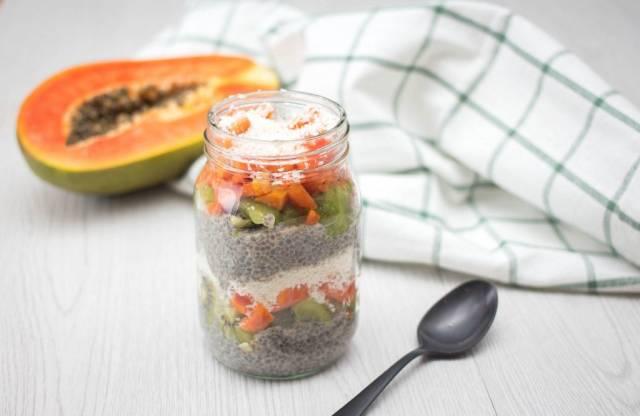 Papaya und Kiwi Chia-Pudding in einem Glas mit Löffel
