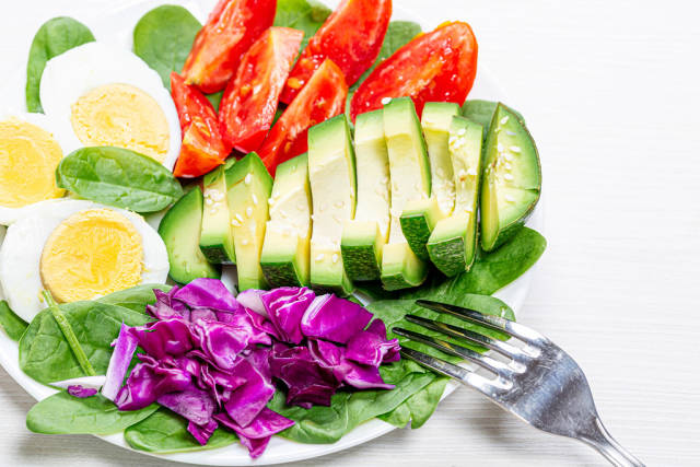 Close-up of pieces of avocado, purple cabbage, tomato with spinach and half boiled eggs