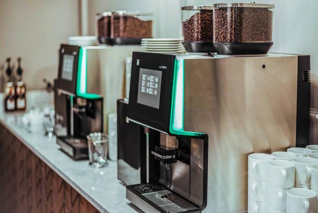 Weiße Tassen neben Kaffeemaschinen