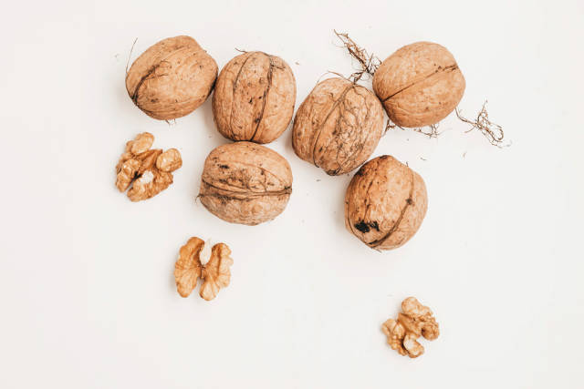 Top view of shelled and whole walnuts on white background
