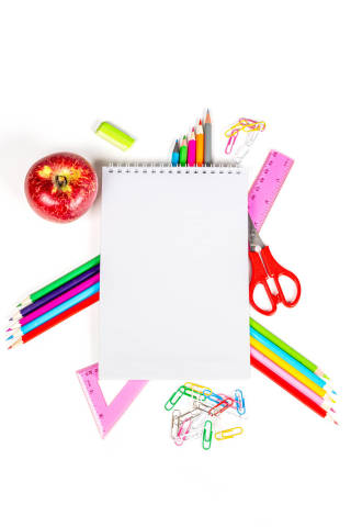 Top view, frame from multicolored school supplies with blank notebook in the middle