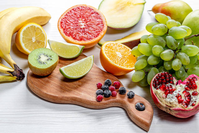 Fresh ripe fruits and berries on white wooden background