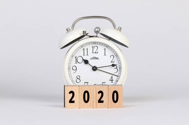 Alarm clock with 2020 text on wooden blocks