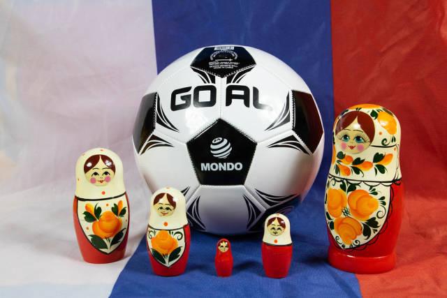 Matryoshka dolls standing around soccer ball on Russian flag