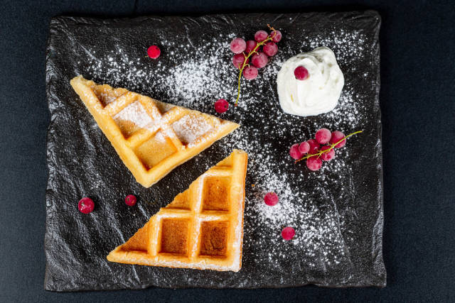 Triangular waffles with currant, powdered sugar and whipped cream on a black background, top view
