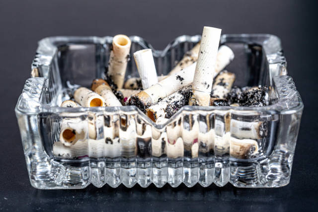 Ashtray with cigarette butts on a black background