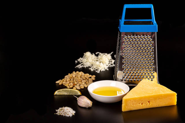 Cooking concept-grater, cheese, pine nuts and spices on a black background