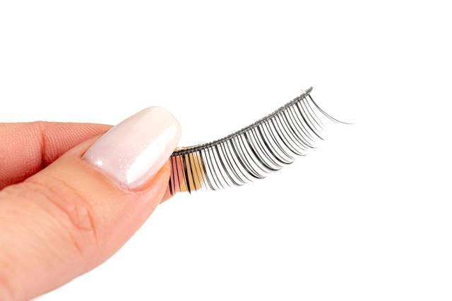 Close up of a womans hand holding false eyelashes