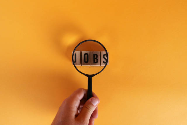 Hand holding magnifying glass over Jobs text