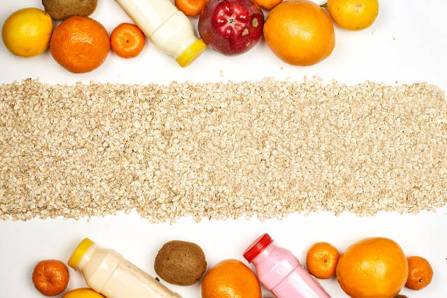 Healthy food background with bottles of detox smoothies and pile of organic fruits