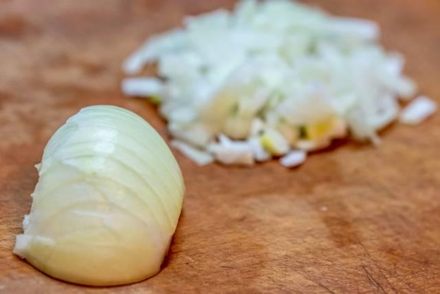 Eine Zwiebel und Zwiebelwürfel auf einer Holzplatte - Bokeh