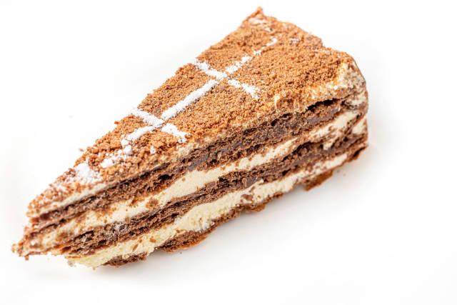 Slice of napoleon chocolate cake on white plate