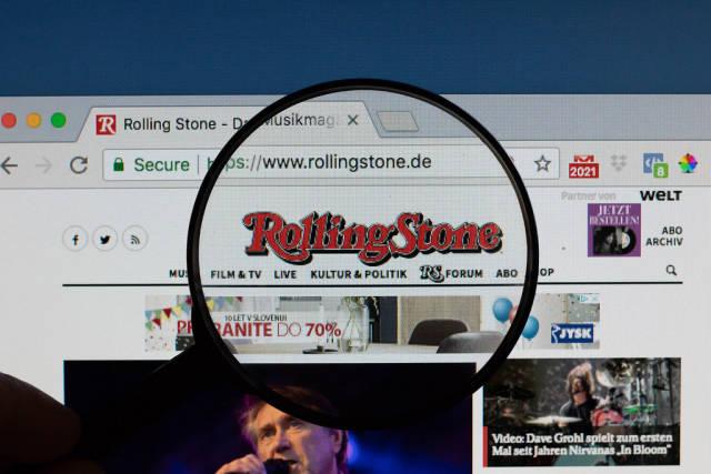 Rolling Stone Logo am PC-Monitor, durch eine Lupe fotografiert