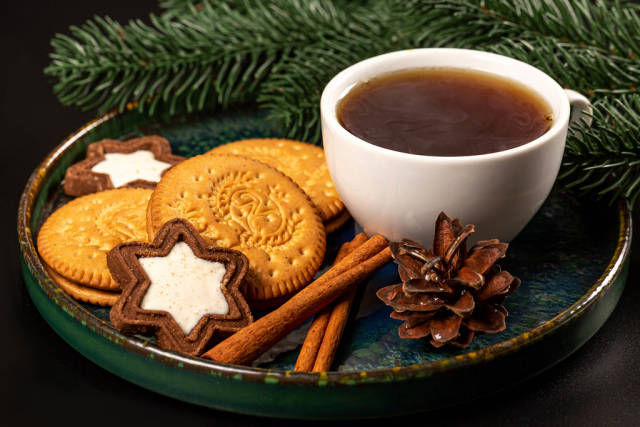 Cup of coffee with cinnamon and cookies on a dark background with branches of a christmas tree