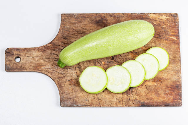 Top view, whole and sliced zucchini on a kitchen board