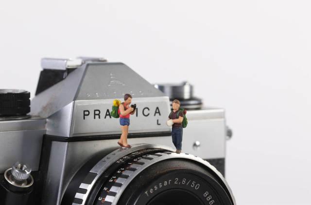 Miniature travelers standing on vintage camera