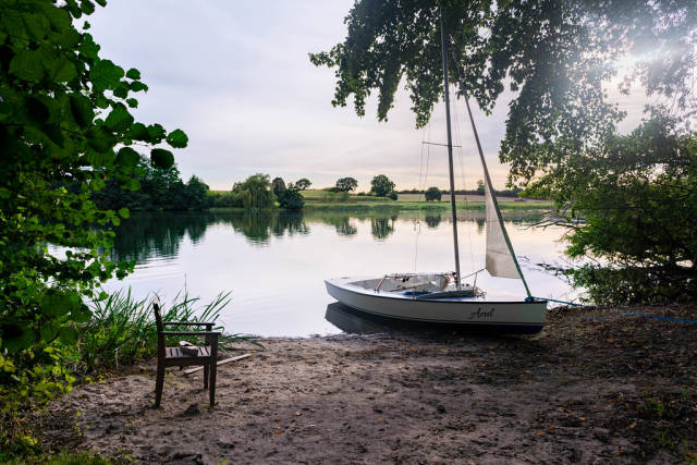 Tranquil and relaxing scene with a wooden chair on the shore next to a boat