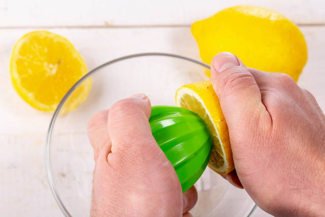Human hands squeeze the juice from half of lemon