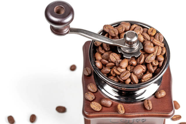 Manual coffee grinder with coffee beans on white background
