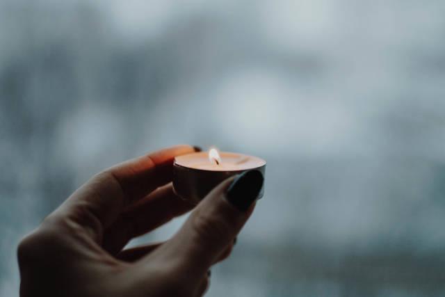 Brennende Kerze in der Hand eines Mädchens, mit einem für den Winter typisch kalten Hintergrund
