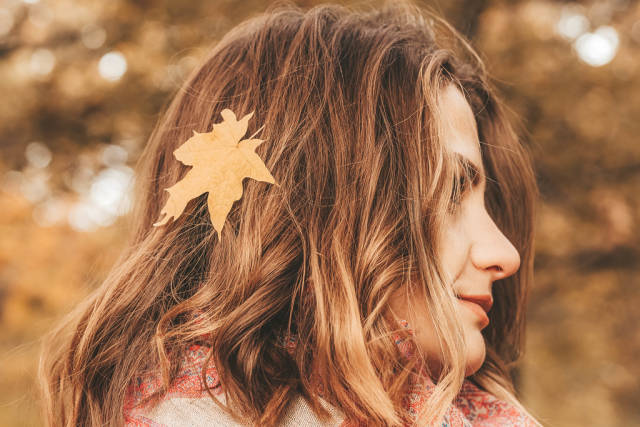 Close-up, portrait of a girl with a yellow leaf in her hair