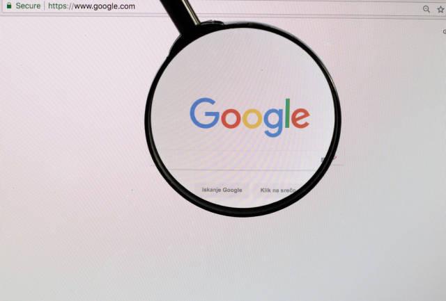 Google-Logo am PC-Monitor, durch eine Lupe fotografiert