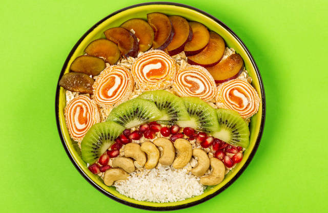 Bowl of oat flakes with plum pieces, turkish delight, kiwi, pomegranate, cashews and coconut on green, top view