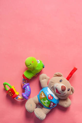 Vertical photo of child rattles with copy space on the top. Bear and snake toys for newborn kids on the pink background. Copy space.