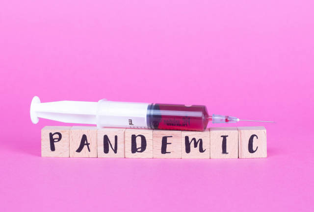 Syringe with wooden blocks and word Pandemic