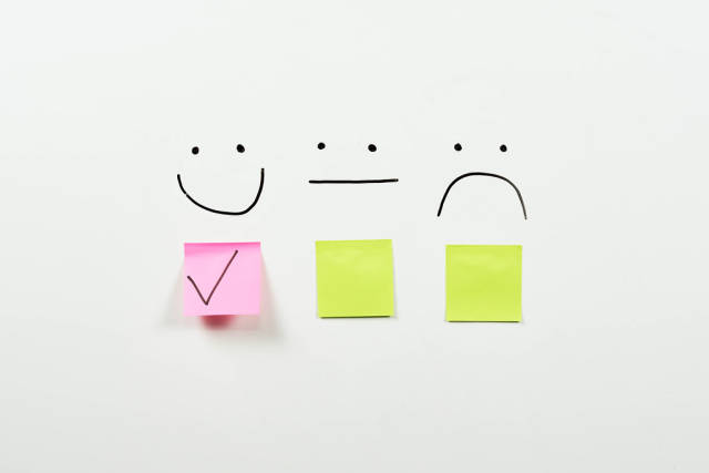 Three smiles on the whiteboard for rating the products or services. Customer review, feedback and satisfaction concepts