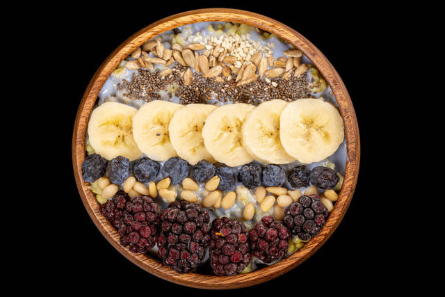 Top view, porridge with seeds, nuts and fruits on black background