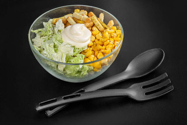 Glass bowl with peking cabbage salad with corn and rusks