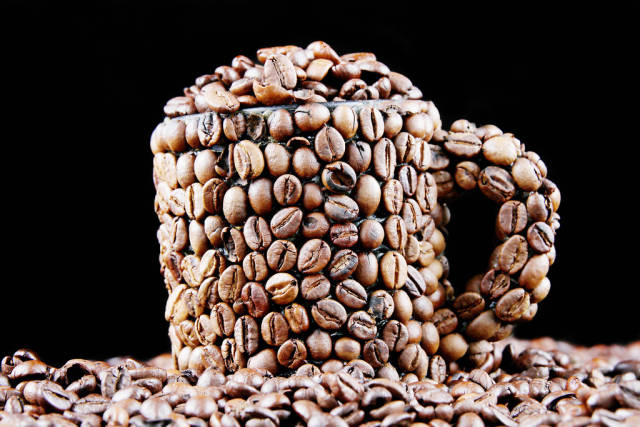 Coffee beans in a cup, black background