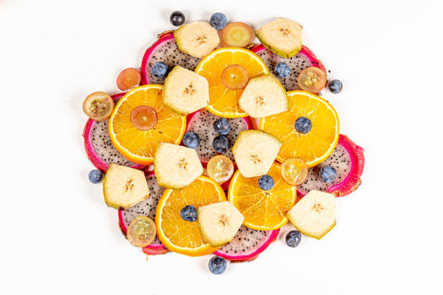 Sliced pitahaya, plantain, tangerine, grapes and blackthorn berries, top view