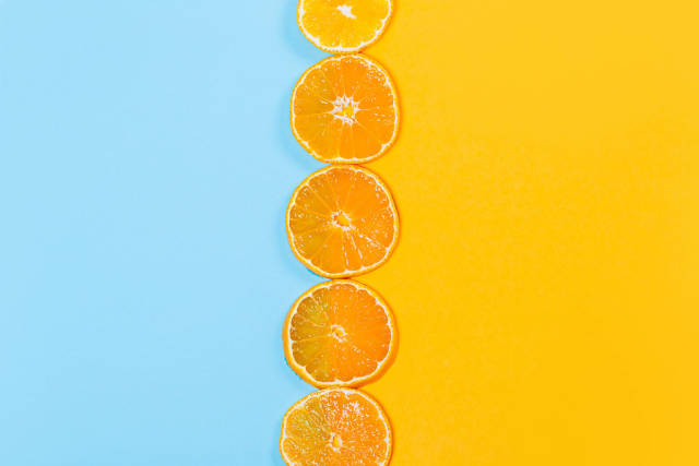 Top view, round pieces of tangerine on orange and blue background