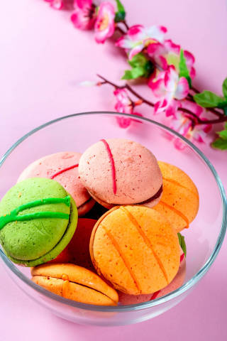 Macaroons cookies with flowers on pink background