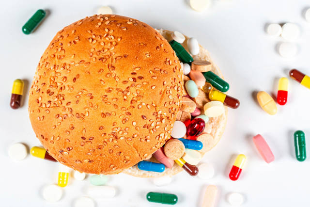 Top view of burger and medical pills and capsules on white background