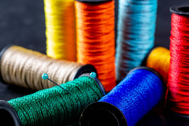 Durable and colorful spools of thread on a black background