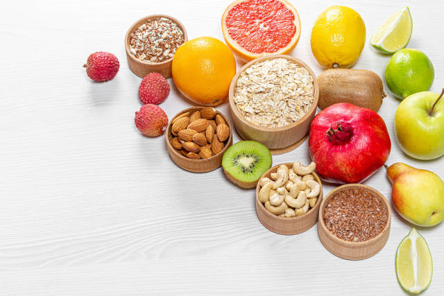 Healthy food ingredients. Fruits, nuts, seeds on wooden white background