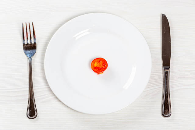 A piece of tomato on a white plate with a knife and fork. Weight loss concept